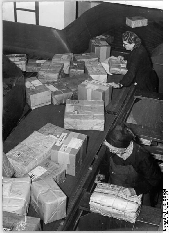 Illus Martin 14.12.51 Modernste Paketbeförderungsanlage im Postamt O 17, Berlin. Im Postamt O 17 Berlin wurde eine mechanische Paketbeförderungsanlage in Betrieb genommen, die täglich 70..000 Pakete befördert. UBz: Gerade jetzt zu Weihnachten, wo der Paketverkehr besonders gross ist, bedeutet die mechanische Beförderungsanlage für die Postangestellten eine grosse Erleichterung. Gleich von der Paketaufgabestelle aus werden die Pakete auf das Förderband gelegt.