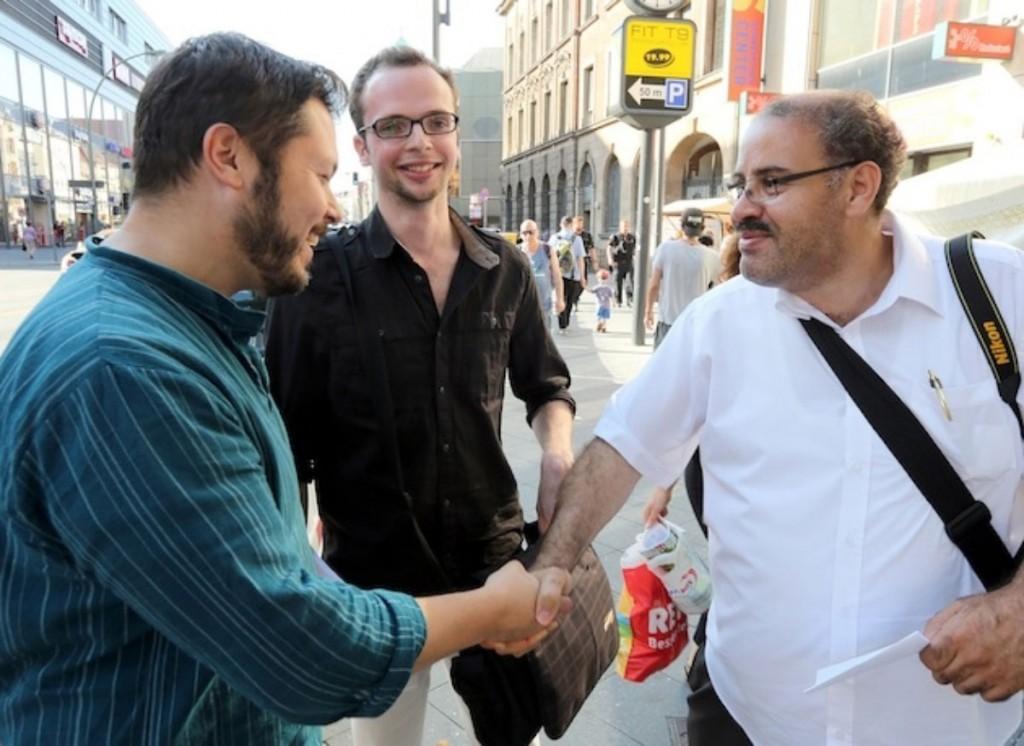Muslimisch-jüdischer Handschlag in Neukölln, im Hintergrund freut sich Armin Langer, Foto: © Salaam Shalom